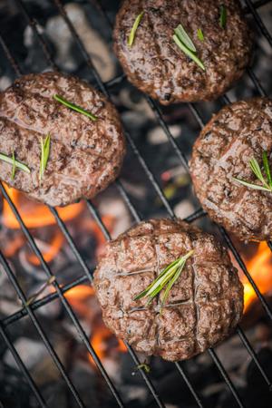 Foto de top view, beef burgers on bbq flames. - Imagen libre de derechos