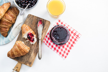 Photo for Fresh croissant with blueberry marmelade served on wooden board - Royalty Free Image