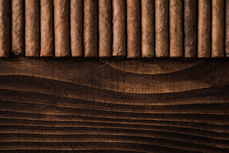 Photo pour Cuban cigars close up on wooden table, border background. Directly from above top view - image libre de droit