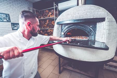 Foto de Bearded man chef preparing pizza at local business. - Imagen libre de derechos