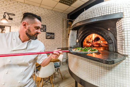Foto de Bearded pizzaiolo man baking pizza in woodfired oven in local pizzeria - Imagen libre de derechos