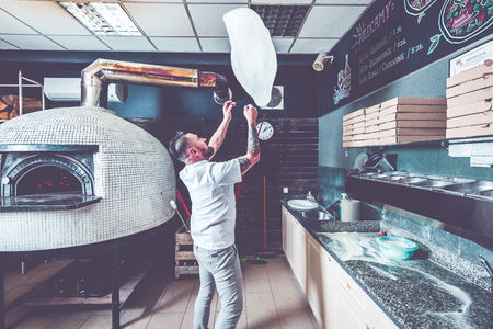 Foto de Bearded pizzaiolo chef lunching dough into air. - Imagen libre de derechos