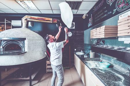 Photo pour Bearded pizzaiolo chef lunching dough into air. - image libre de droit