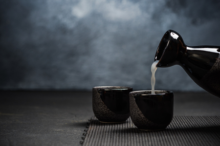 Photo for Pouring sake into sipping ceramic bowl. - Royalty Free Image