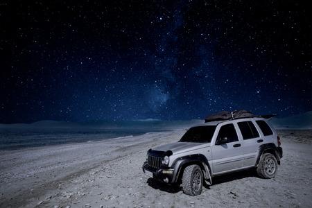 Photo pour Off road car on beach under MIlky Way night sky - image libre de droit