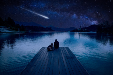 Foto de Man with dog looking at Perseid Meteor Shower at lake Bled - Imagen libre de derechos