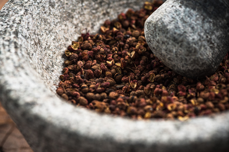 Photo pour Timut sihuan pepper seeds in granite pestle or mortar. - image libre de droit