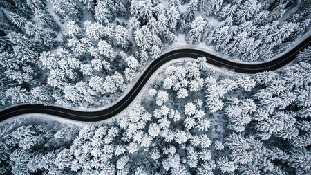 Photo pour Curvy windy road in snow covered forest, top down aerial view. - image libre de droit
