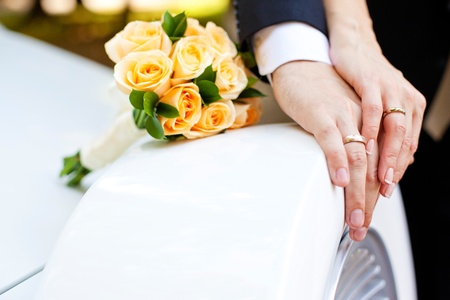 Photo pour Hands of bride and groom with rings and bouquet of flowers - image libre de droit