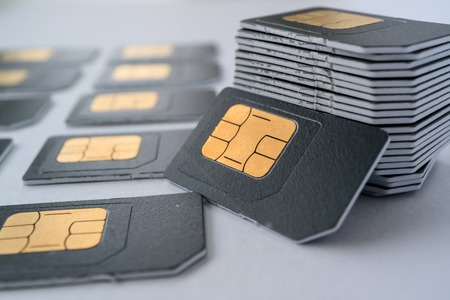 Photo pour SIM cards for mobile phones in one stack leaning against the stack, gray card - image libre de droit