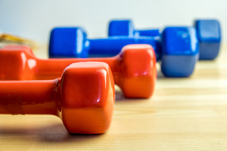 Foto per Dumbbells lined up, sports at home, red and blue dumbbells - Immagine Royalty Free