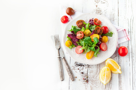 Foto per Fresh salad with cherry tomatoes, spinach, arugula, romaine and lettuce in a plate on white wooden background, top view - Immagine Royalty Free