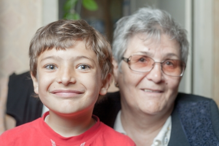 portrait of a senior woman and her grandson indoors