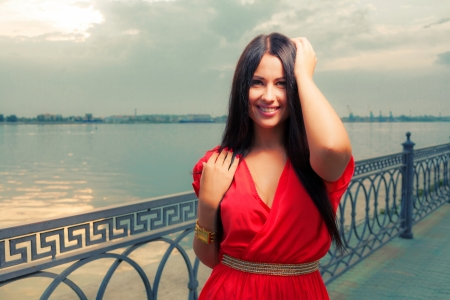 Adorable brunette with red dress posing on a dawn on riverside near water   Fashion Beauty  Outdoors shot