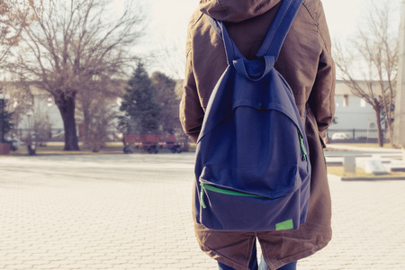 Foto de Rear view of hipster girl carring backpack on her back, copyspace. - Imagen libre de derechos