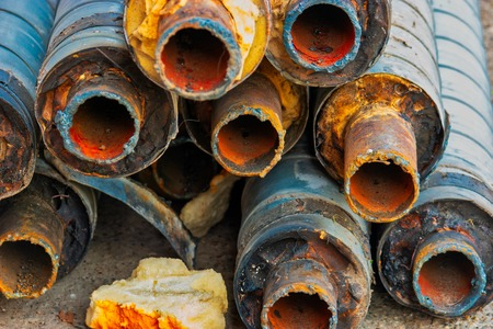 Photo for Water Pipeline repair. Large rusty steel pipe with insulation on the construction site in a plastic tube wrapper lying on the yard in a bunch horizontally. Rusty old pipeline stacked up - Royalty Free Image