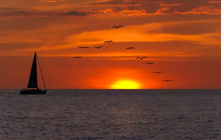 Photo pour Sailboat sunset fantasy with a sulhouetted boat sailing along its journey aagainst a vivid colorful sunset with birds flying in formation against an orange and yellow color filled sky. - image libre de droit