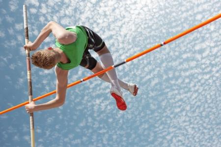 Photo pour Young athletes pole vault seems to reach the sky - image libre de droit