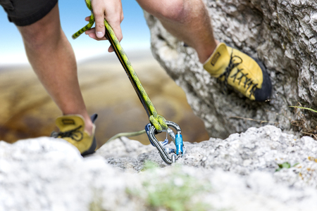 Climber reaches the summit of a mountain. Focus is on the rope and the carabiner