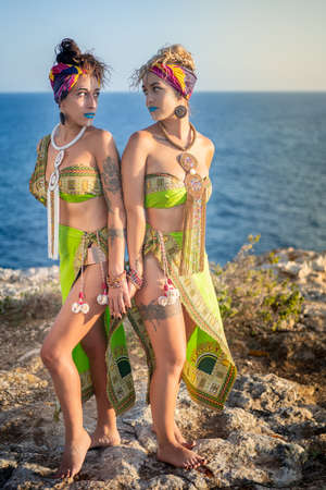 Foto de Two beautiful young women with african clothes and makeup, typical of belly dance, looking into each other's eyes while holding hands - Imagen libre de derechos