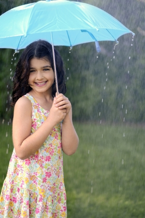 young girl playing in rain with umbrella