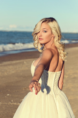 Photo for blonde woman in white dress follow me on beach - Royalty Free Image