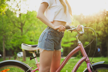 Photo for Beautiful woman with bicycle on the meadow in the park. Closeup picture - Royalty Free Image