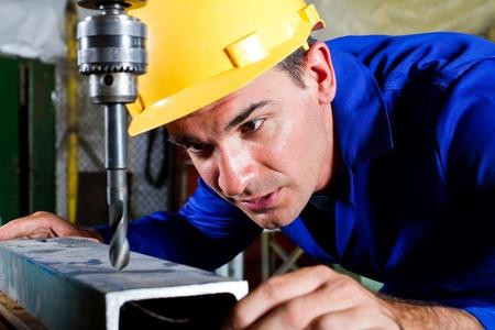 male metal worker using drillpress