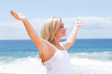 Photo pour carefree young woman with arms open on beach - image libre de droit