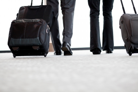 Photo pour business travellers walking in airport with luggage - image libre de droit