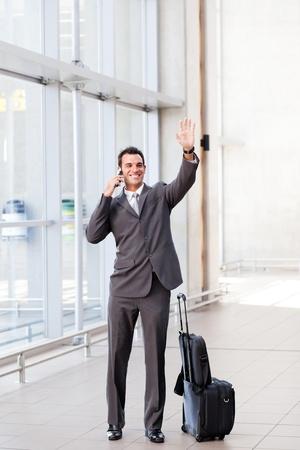 Photo pour young businessman waving good bye at airport - image libre de droit