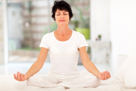 Photo for beautiful middle aged woman meditation on bed at home - Royalty Free Image