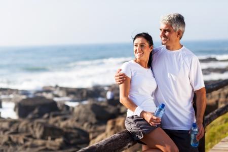 Photo pour happy mature couple relaxing after exercise at the beach - image libre de droit