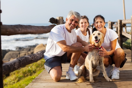 sporty family and their pet dog at the beach in the morning