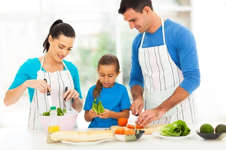 lovely young family preparing food in kitchen at home
