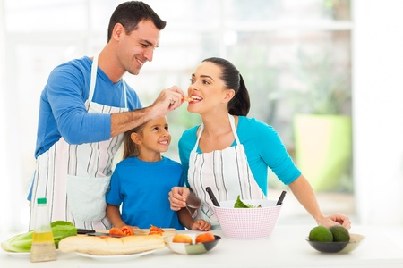 loving husband feeding wife a piece of tomato while cooking with daughter