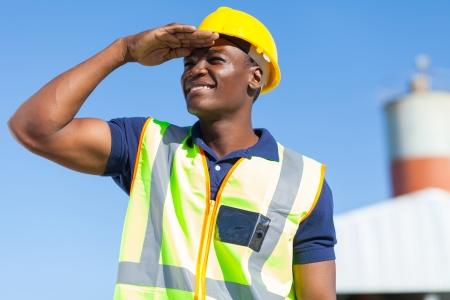 Photo pour smiling african builder looking into distance - image libre de droit