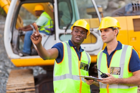 Foto per co-workers talking at construction site with bulldozer behind them - Immagine Royalty Free