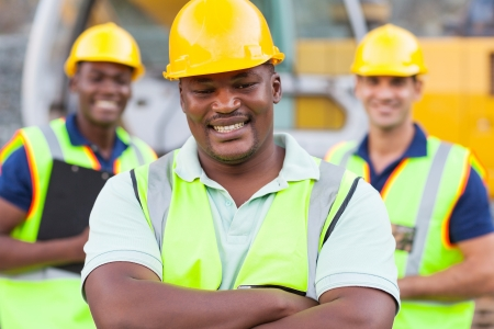 Photo pour smiling african construction worker with colleagues - image libre de droit
