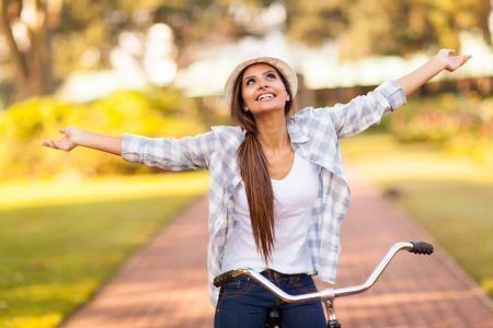 pretty young woman enjoying riding bike at the park with arms outstretched