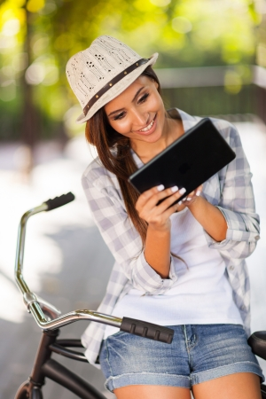 cheerful young woman using tablet computer outdoors