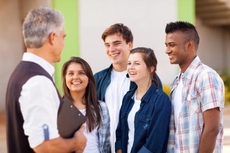 Photo pour middle aged high school teacher talking to students during break - image libre de droit