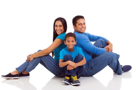 happy indian family sitting on the floor isolated on white