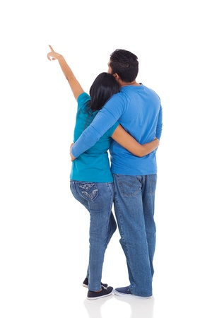 rear view of young couple pointing at copy space over white background