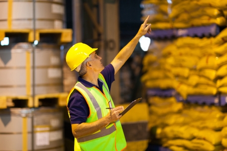 Photo for middle aged shipping company worker counting pallets in warehouse before dispatching - Royalty Free Image