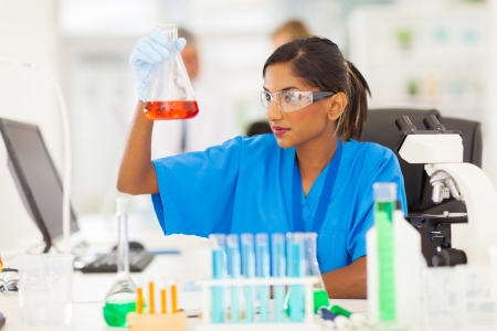 Foto de beautiful young indian medical researcher analyzing liquid in a flask - Imagen libre de derechos