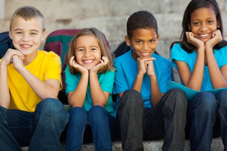 Photo for cheerful primary school children sitting outdoors - Royalty Free Image