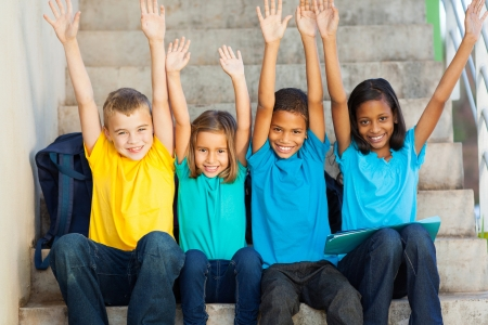 Photo pour group of happy primary students with hands raised sitting outdoors - image libre de droit