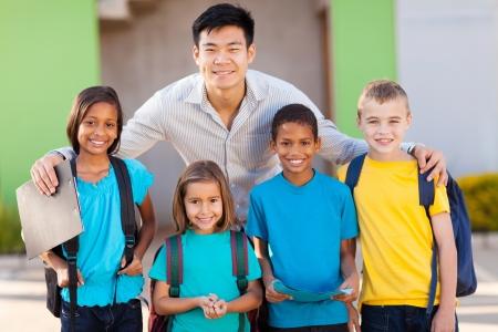 Foto de four elementary school students and teacher on campus - Imagen libre de derechos