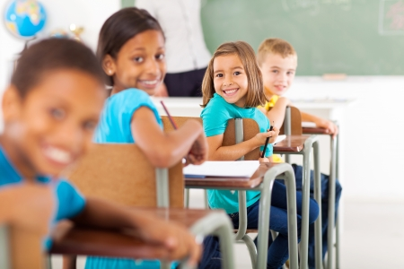 Foto de group of primary school students in classroom looking back - Imagen libre de derechos